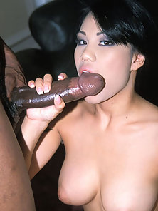 Cute asian girl takes a black penis in her mouth and pussy