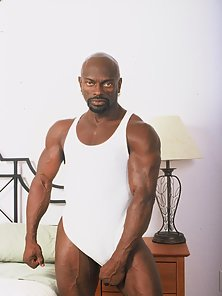 Muscle bound black gay Darell strips naked in bed to show off his juicy looking dick