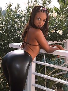Captivating ebony babe strips her tight leather pants and shows pussy outdoors