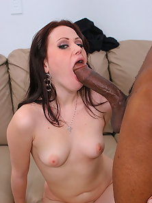 Young brunette slut rides a stiff black cock on the sofa